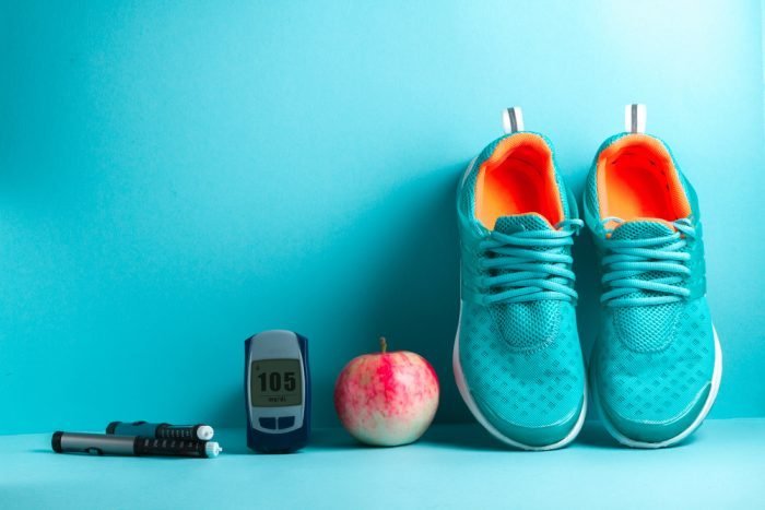 a blood sugar tester, apple, and shoes,