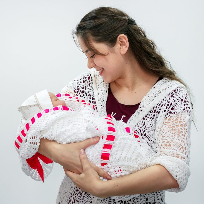 a mother holds her swaddled child