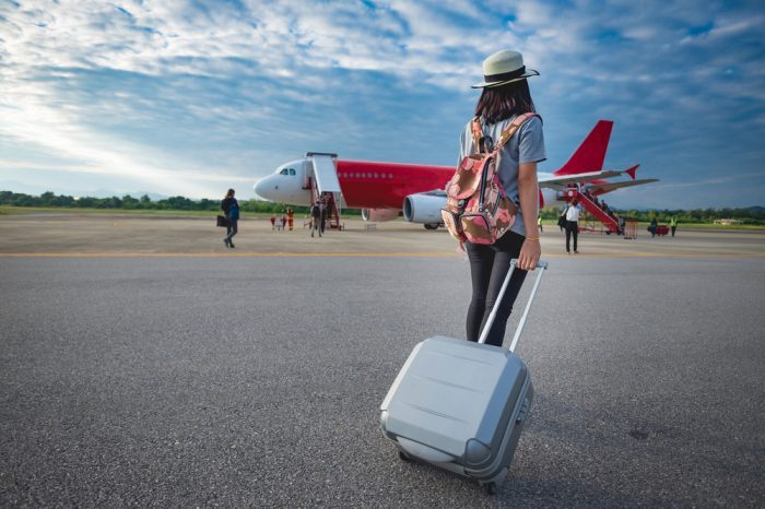 young woman pulling suitcase across tarmack to plane