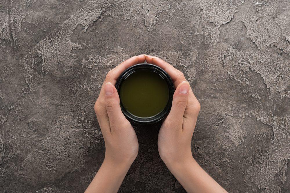 hands holding mug of green liquid