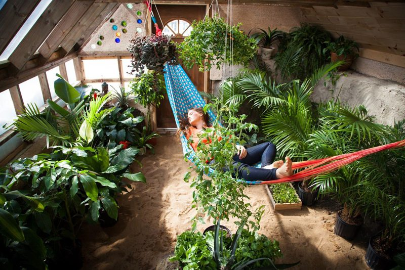woman reclining on hammock in greenhouse