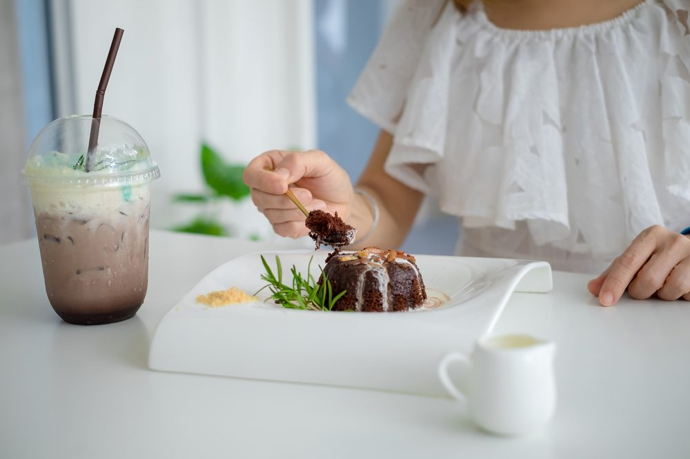 woman about to eat a delectable brownie