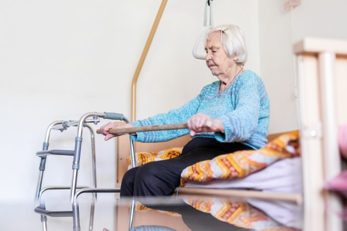 older woman doing exercises with cane