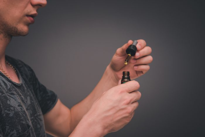 how to use cannabis oil demonstrated by oyung man using dropper