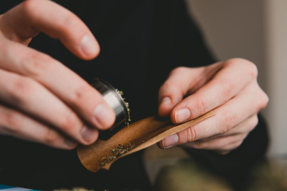 person rolling a blunt