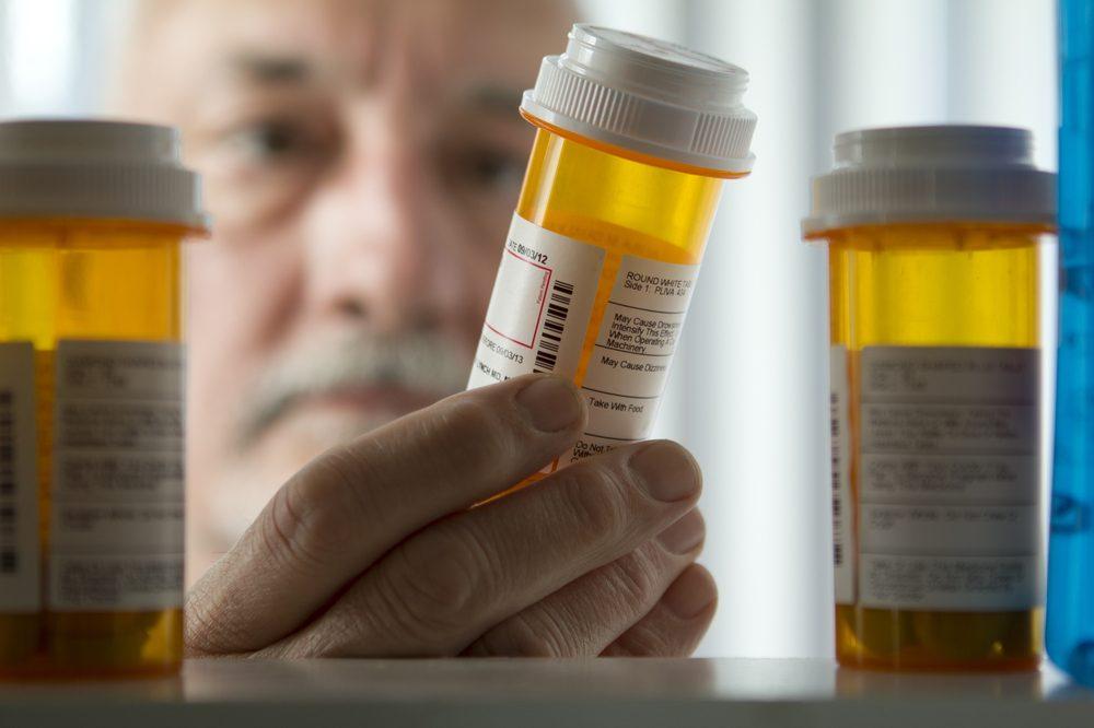 older adult looking in medicine cabinets