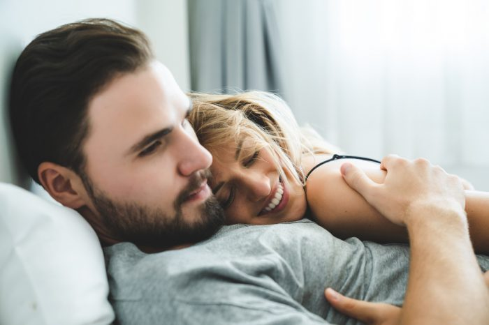 sex and cannabis represented by young couple laying down and hugging happily