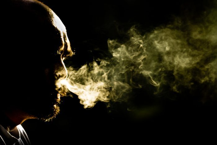 man in darkness smoking to show that smoking kills
