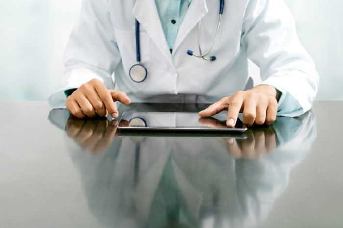 standardized medicine represented by the figure of a doctor on ipad
