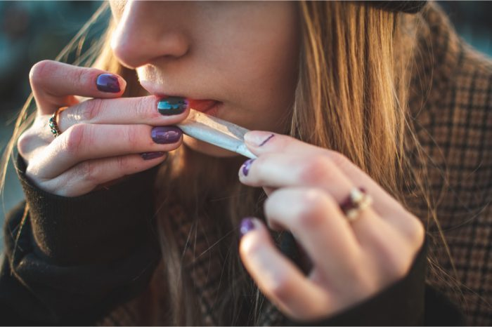 cannabis and mental health concept represented by young woman rolling joint