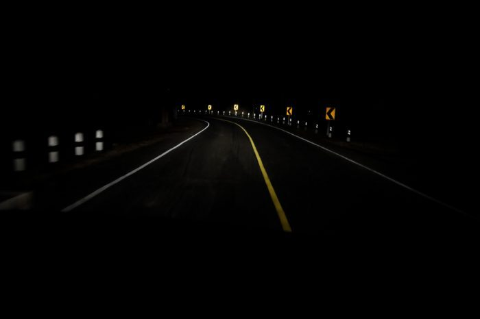 driving impaired represented by dark winding road