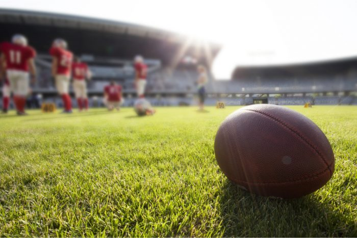 football sitting alone on green field to represent weed ban for NFL players