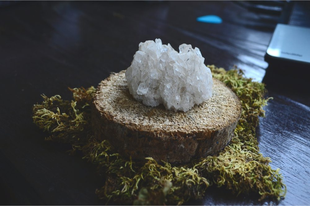 CBD crystals on a stump next to cannabis buds