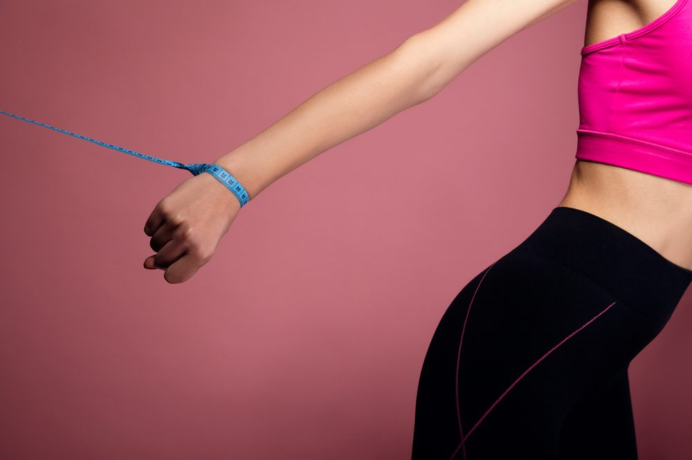 anorexia vs bulemia represented by girl pulled back by tape measure around wrist