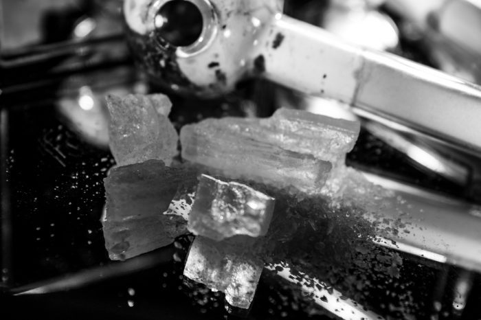 brain damage from meth represented by meth crystals and pipe