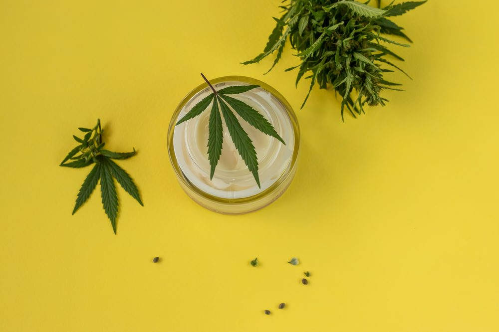 cbd cream in canister with cannabis leaves