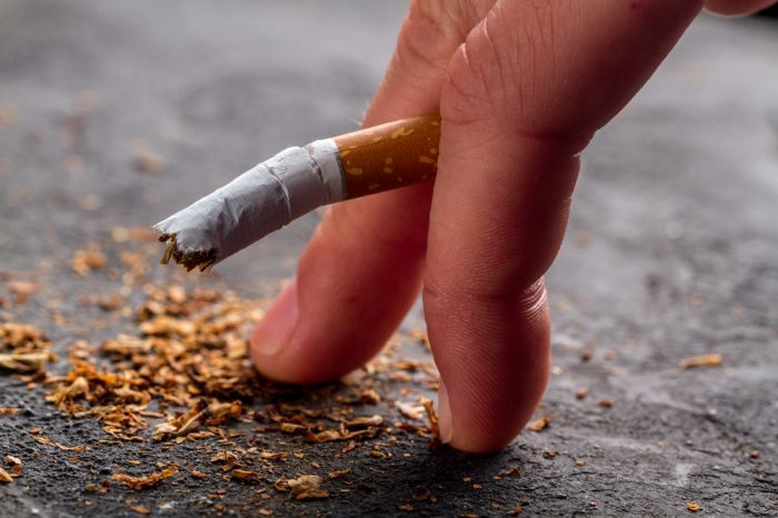 First of all, impotent looking cigarette between fingers of man's hand.