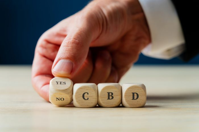 is cbd legal in my state represented by hand turning blocks with cbd on them
