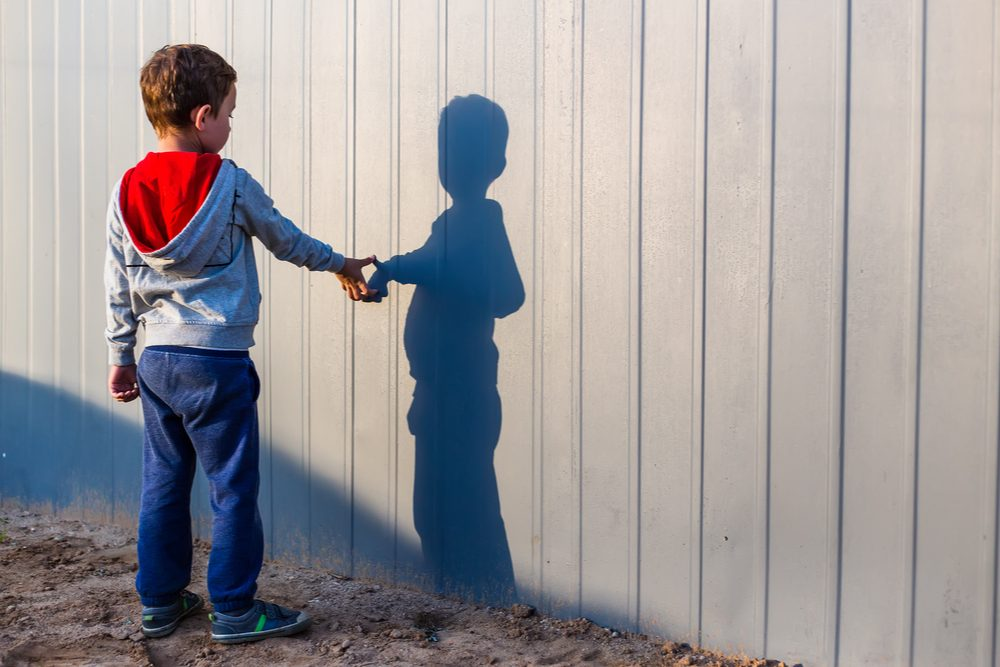 SHOULD WE TREAT AUTISM represented by young boy looking at and playing with shadow