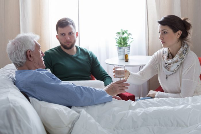 terminally ill patinets like this white man being given a glass of water in bed with his family by his side are great cannabis patients