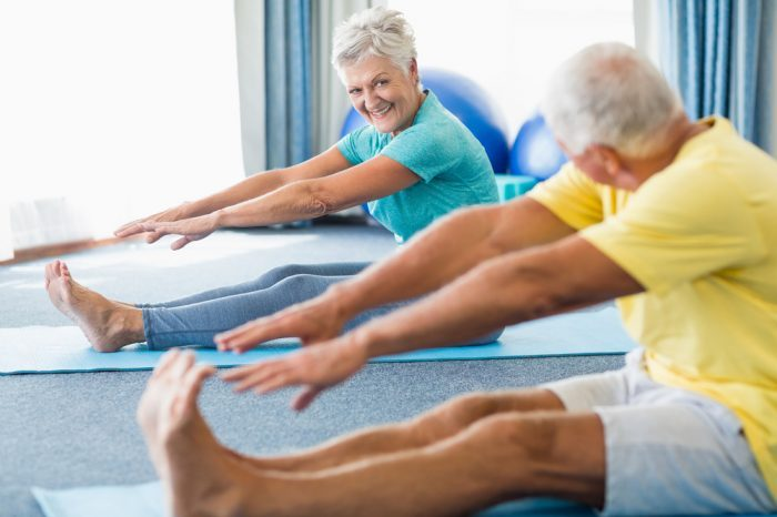 jhuman cbd receptors helping older adults stretching in a yoga class