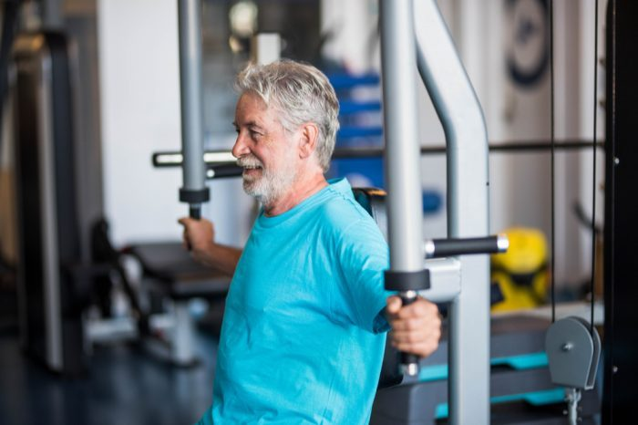 older white man working on muscle development in gym