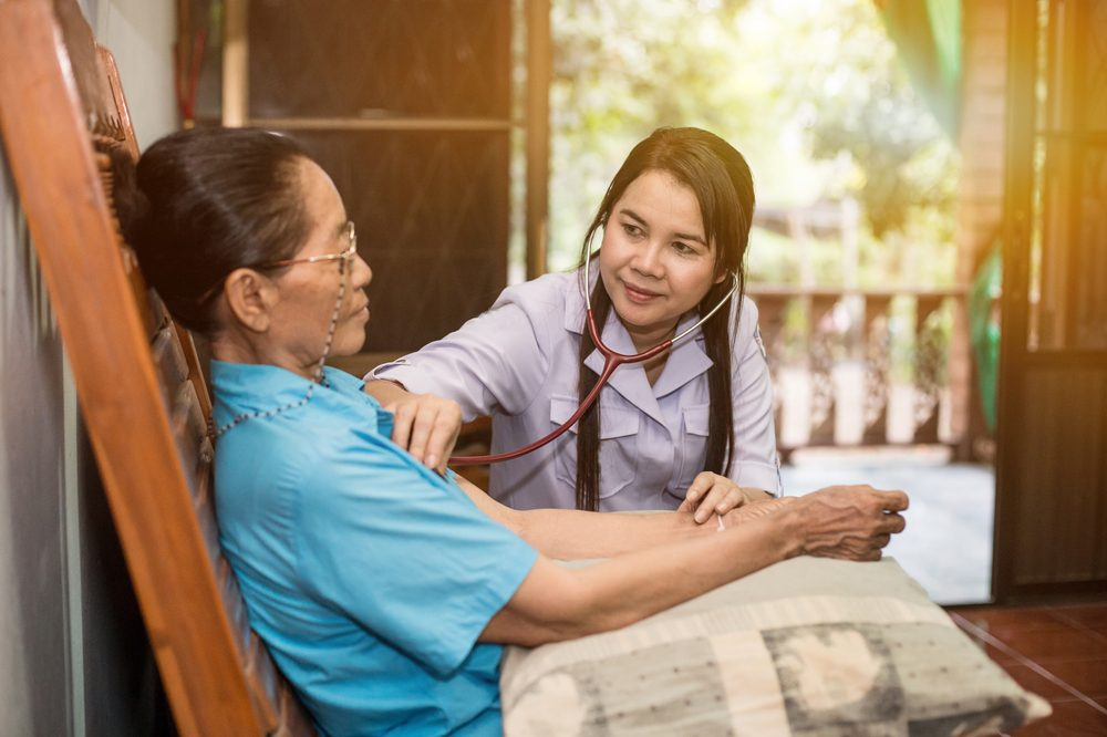 traditional thai medicine represented by young woman checking heartbeat of older woman