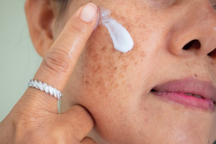 STOP AGING with hemp cream like this which an older asian woman is applying