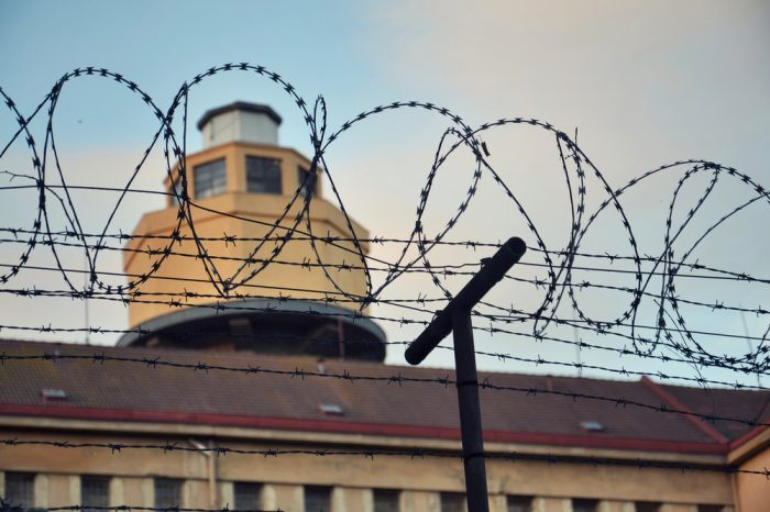 addiction in prison represented by prison viewed through barbed wire
