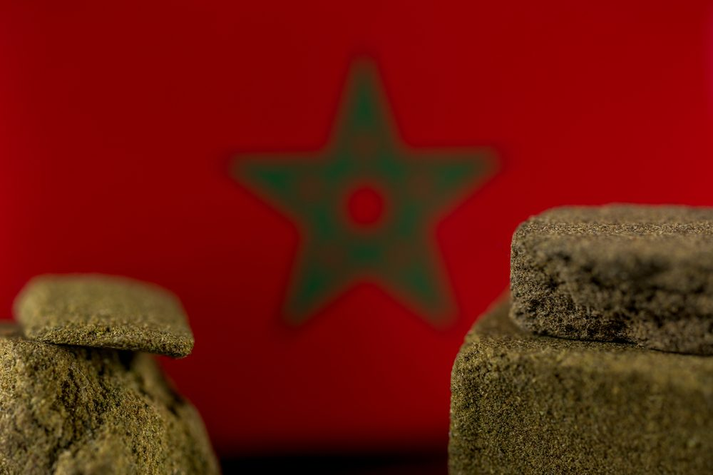 Some cannabis hash with a Moroccan flag in the background. Some of the best hashish comes from the North African country