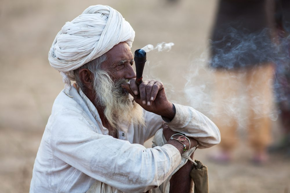 An old man bearded man smokes from a hash pipe. Cannabis hash originates from Central Asia