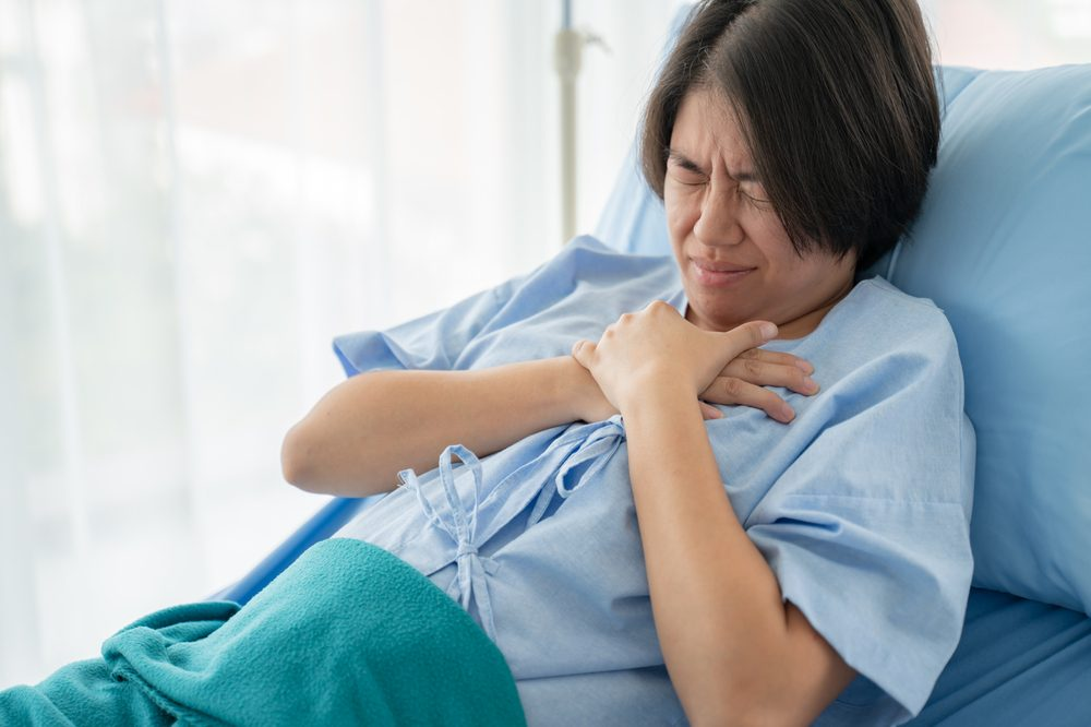 Woman grips her chest in pain. Caring for patients with cardiovascular disease can be helped with medical cannabis