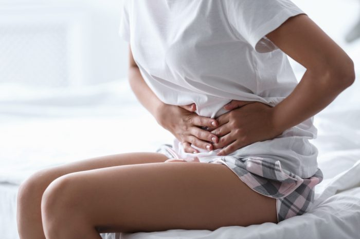common pelvic conditions represented by young woman feeling pain in her stomach