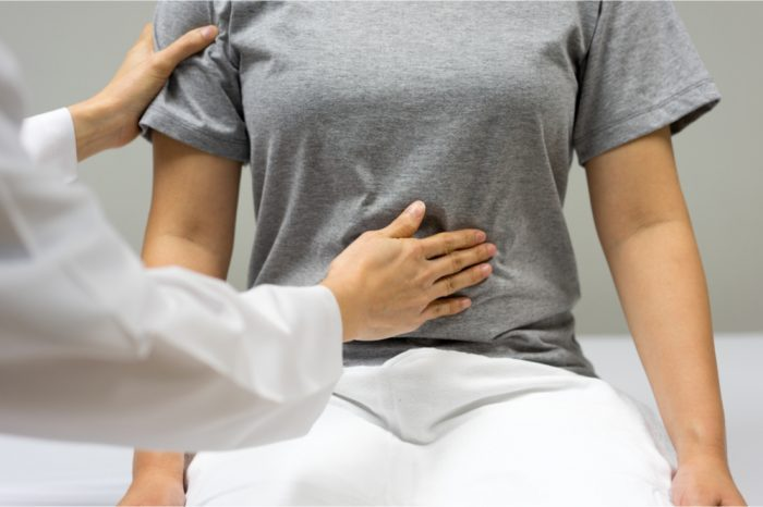 common pelvic conditions represented by doctor feeling stomach of woman on table