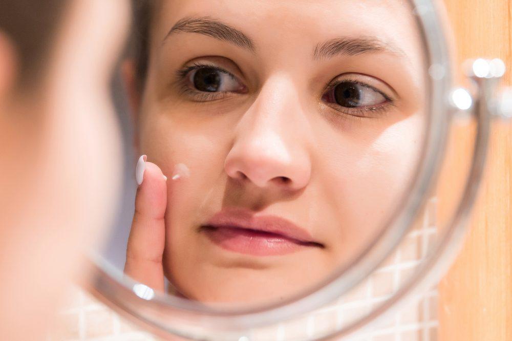 how to get rid of pimples represented by young female puttign cream on face