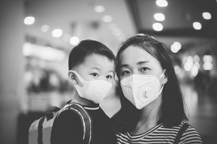 human coronavirus treatment represented by asian mother and child in masks