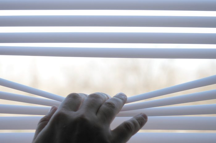 mental health and isolation represented by hand pulling down blinds