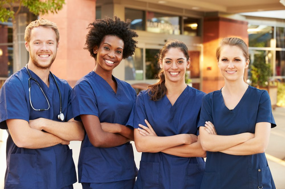 Four nurses stand outside a hospital. Nurses and midwives are being honoured this World Health Day ojn April 7th.