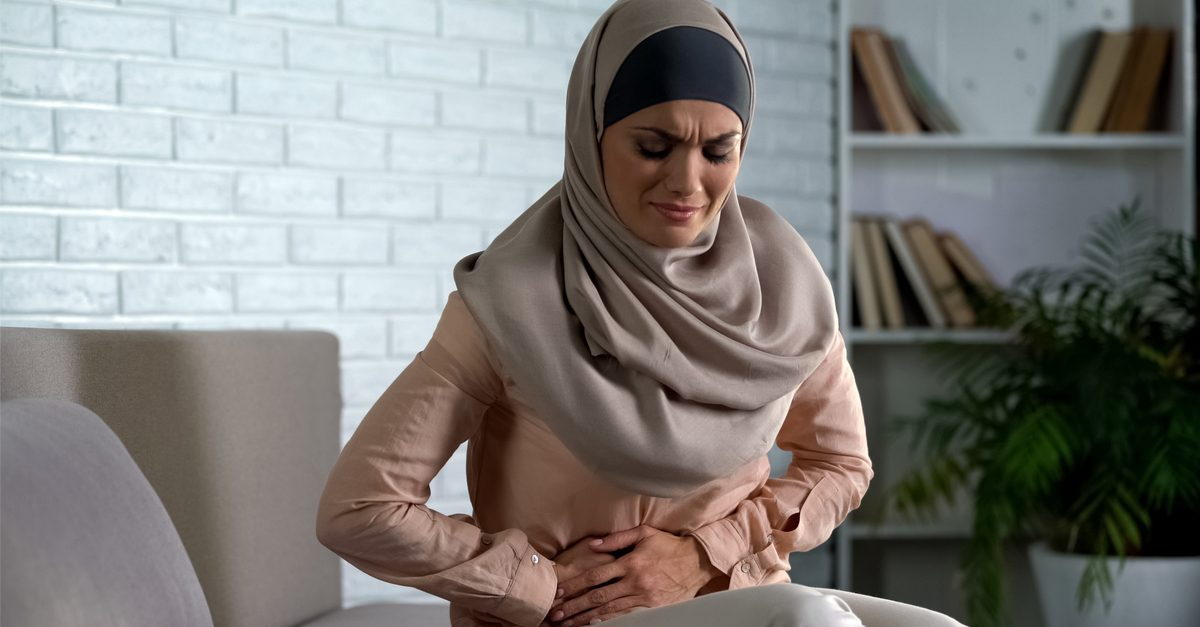 young arabic woman in hijab holding stomach over potential period symptoms