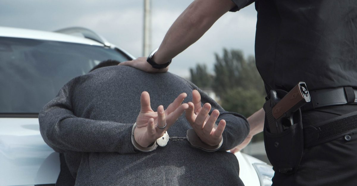 police funding represented by officer pushing black or latinx man onto back of squad car