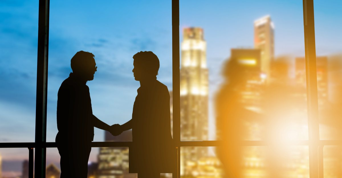 Systemic discrimination represented by business leaders shaking hands against window, silhouetted. They can help make a difference.