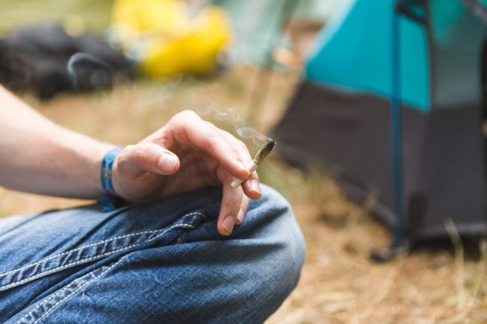 camping with cannabis represetned by hand of white person with joint, with tent in backgroound