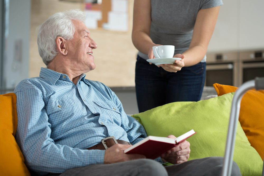 medicine for elderly people represented by an elderly man sitting on the couch reading and a person bringing him tea