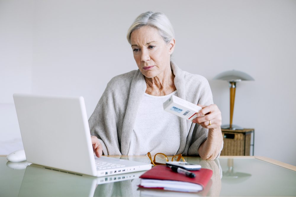 buy cannabis online represented by older white female looking at laptop with debit card