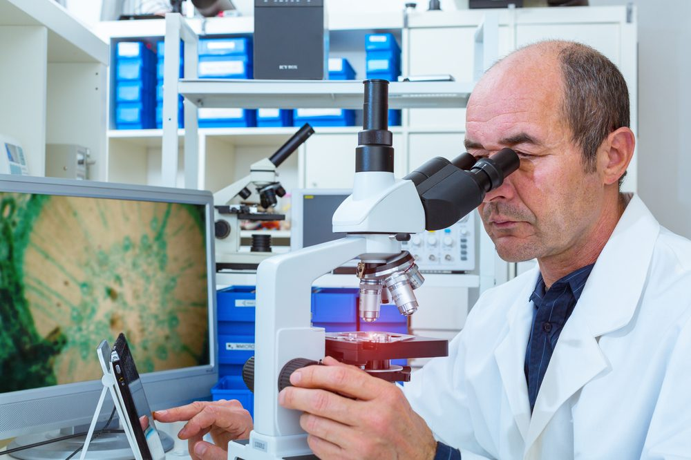 cannabis cures cancer represented by older white scientist lookign into microscope