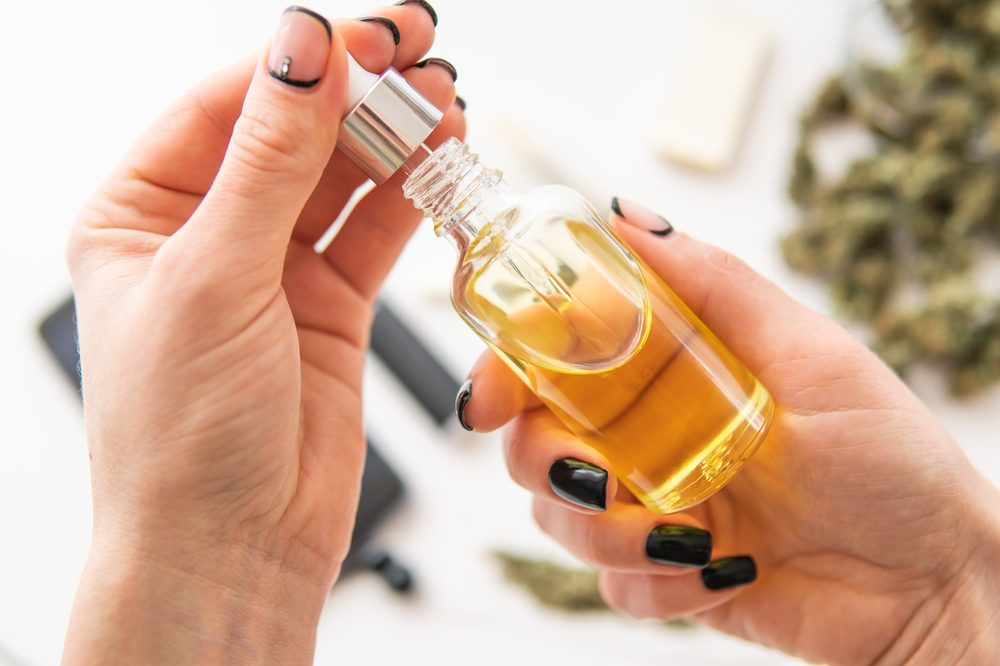 cbd use during pregnancy and cbd's impact on women's health represented by white female hands looking at CBD bottle