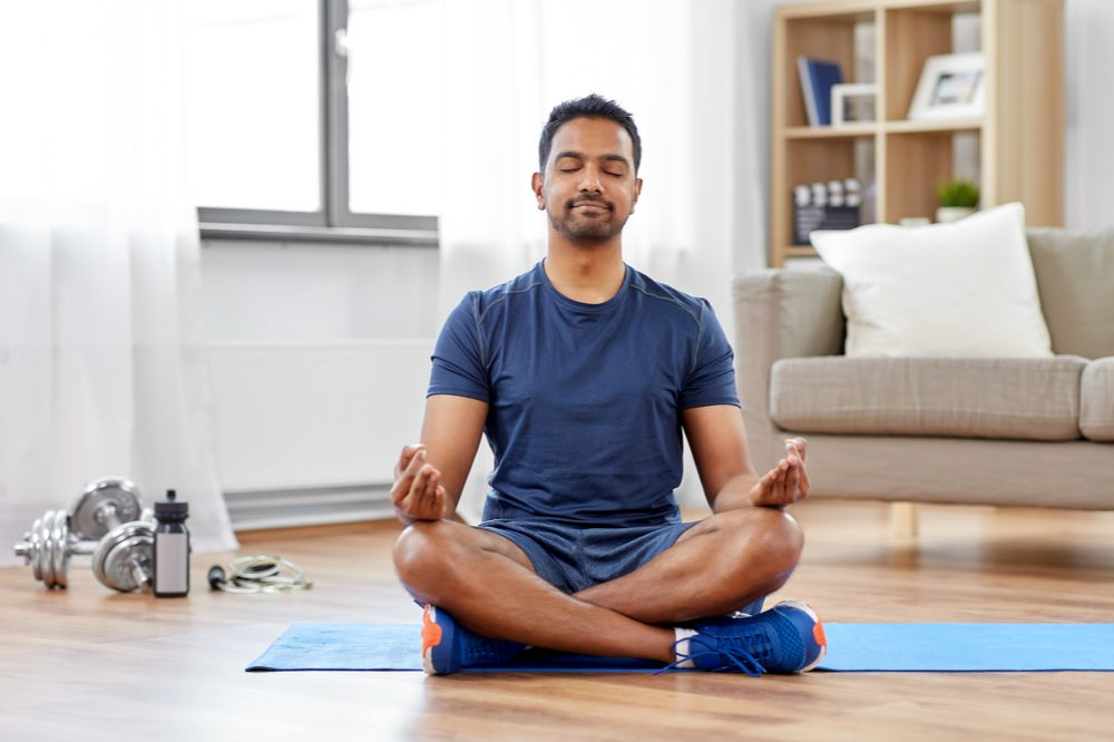 how to heal the mind body and spirit represented by hispanic man meditating next to yoga mat and weights