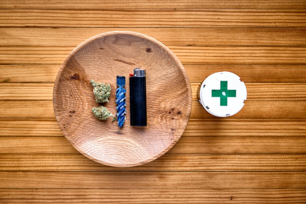 how to smoke cannabis represented by lighter weed and pipe sitting next to green grinder