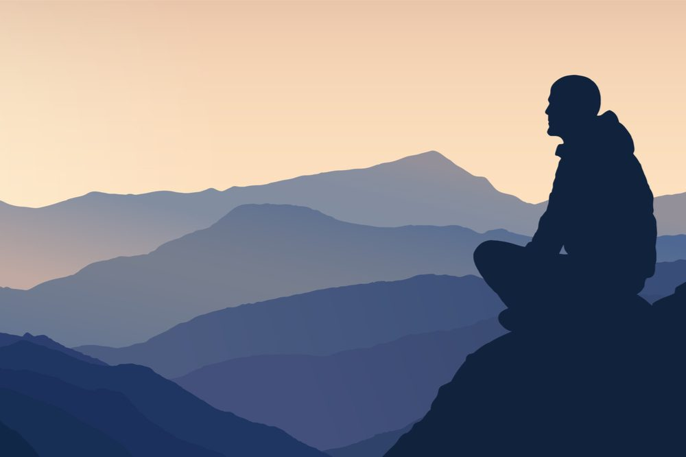peak spiritual experience represented by silouhette of person meditating on mountaintop