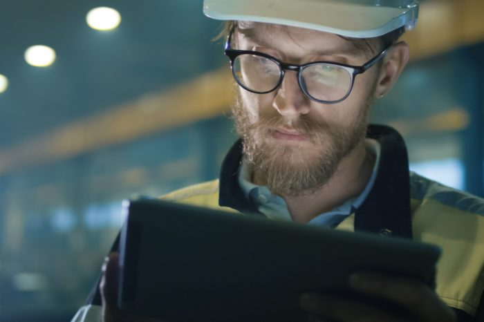 cannabis at work represented by white man in safety gear on ipad in industrial job